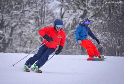Juan Cruz Adrogue en esquíes y Julio Viola (h) en snowboard